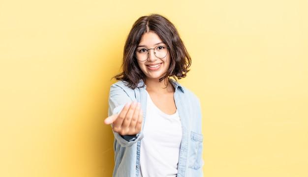 Молодая красивая девушка чувствует себя счастливой, успешной и уверенной в себе, сталкивается с проблемой и говорит: давай! или приветствуя вас