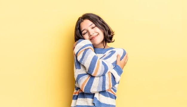Молодая красивая девушка чувствует себя влюбленной, улыбается, обнимает и обнимает себя, остается одинокой, эгоистичной и эгоцентричной