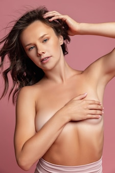 Young pretty girl female naked model isolated over pink studio wall natural beauty