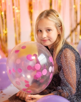 Young pretty girl at festive party with balloons