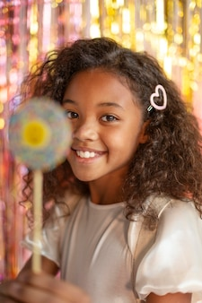 Young pretty girl at festive party with lollipop