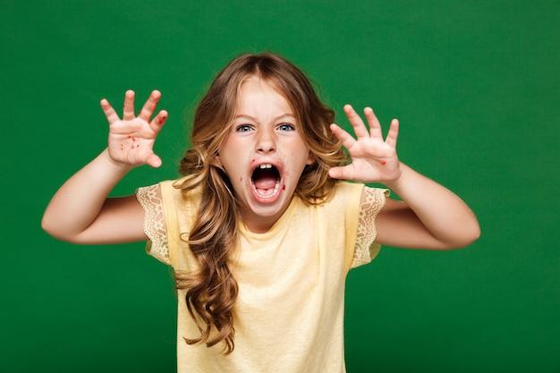 Giovane ragazza graziosa che spaventa sopra la parete verde