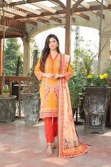 Молодая симпатичная девушка в оранжевом камэз шальвар, полная передняя фотография