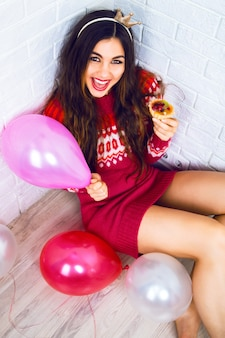 Молодая красивая девушка веселится на вечеринке по случаю дня рождения, в повседневном свитере с короной для вечеринки, с розовым воздушным шаром и вкусным маленьким фруктовым пирогом. положительные эмоции, читаем к празднику.