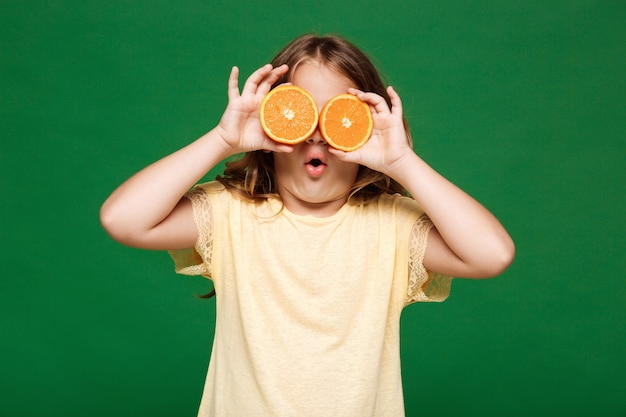 Young pretty girl hiding eyes with oranges over green wall