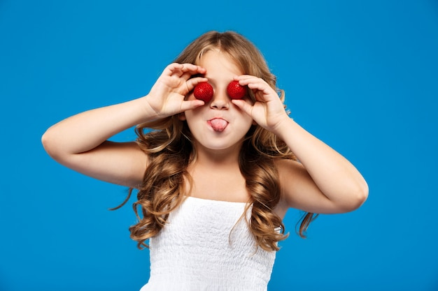 青い壁にイチゴの目を隠す若いきれいな女の子