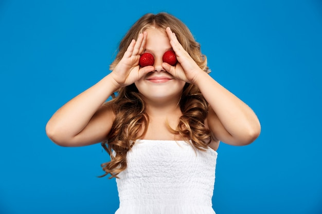 Молодая красивая девушка, скрывая глаза с клубникой над синей стеной
