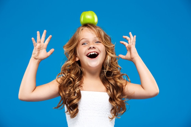 Young pretty girl holding apple on head over blue wall