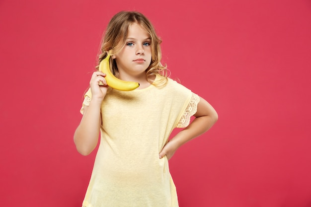 Молодая милая девушка держа банан как телефон над розовой стеной