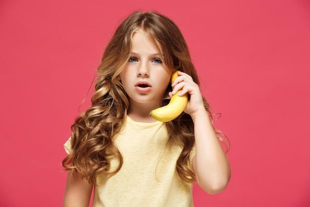 La giovane banana graziosa della tenuta della ragazza gradisce il telefono sopra la parete rosa