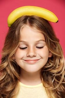 Молодая милая девушка держа банан на голове над розовой стеной
