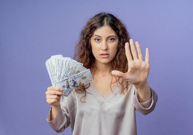 Giovane ragazza graziosa che tiene contanti e che mostra il gesto di arresto