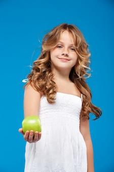 Молодая милая девушка держа зеленое яблоко над голубой стеной