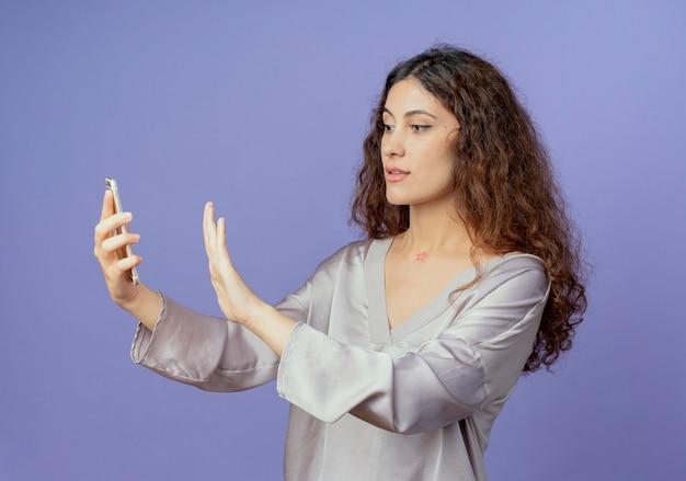 Giovane ragazza graziosa che tiene e che esamina telefono e che mostra il gesto di arresto isolato sull'azzurro