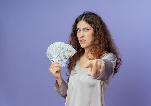 Giovane ragazza graziosa che tiene soldi e che ti mostra gesto isolato sulla parete blu