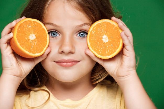 Молодая милая девушка держа апельсин над зеленой стеной