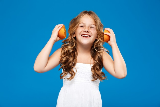 Young pretty girl holding oranges, smiling over blue wall