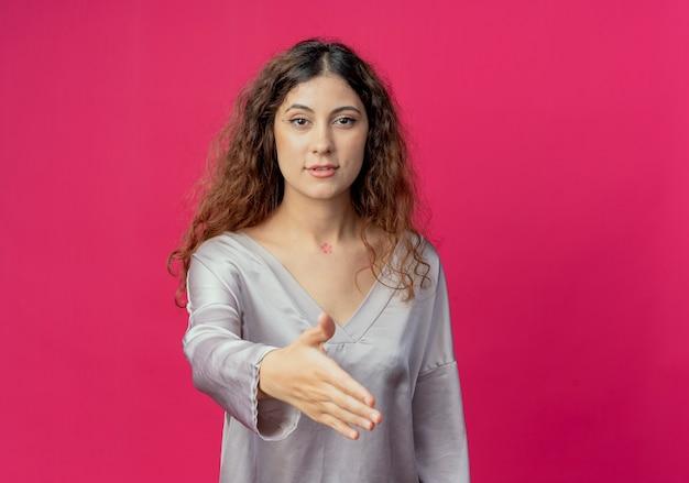 Giovane bella ragazza tendendo la mano isolata sul muro rosa