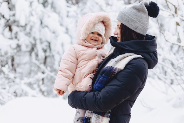 Young pretty girl holds small baby on her hands in winter
