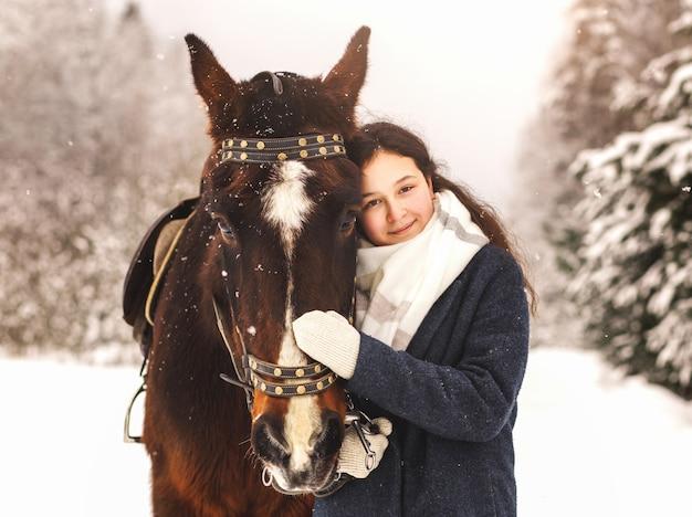 若いかわいい女の子は自然の中で冬に馬を抱きしめます。自然や動物とのコミュニケーション