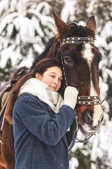 Young pretty girl hugs horse in winter in nature