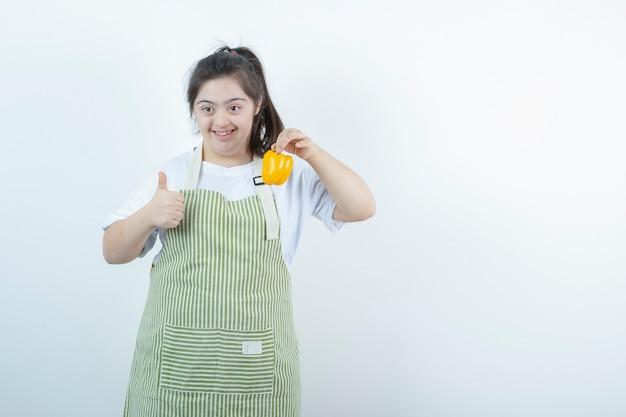 노란색 피망을 들고 엄지 손가락을 보여주는 체크 무늬 앞치마에 젊은 예쁜 여자.