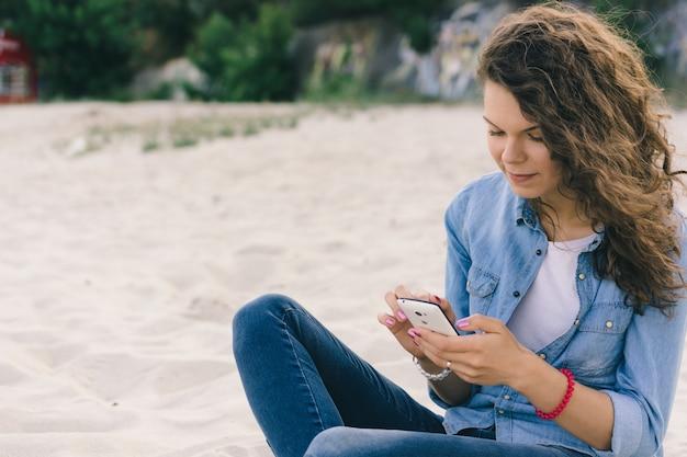 Молодая красивая девушка в джинсовой одежде с помощью мобильного телефона на пляже
