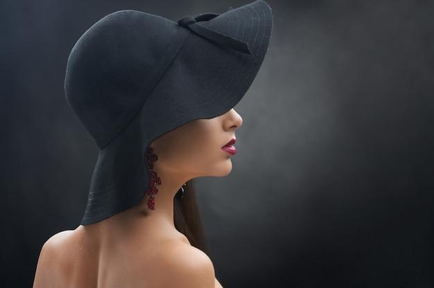 暗い灰色の壁に黒い帽子の若いきれいな女の子。彼女は明るいバーガンディの口紅と豪華なイヤリングを着ています。モデルは細身で、肩と首が裸です。