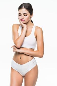 Молодая красивая девушка в белом нижнем белье имеет головную боль, изолированные на белой стене
