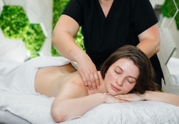 A young pretty girl is enjoying a professional cosmetological massage at the spa