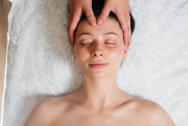 A young pretty girl is enjoying a professional head massage at the spa