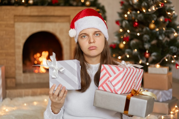 Young pretty girl is not satisfied with her gifts, posing near fireplace and x-mas tree with present boxes in hands