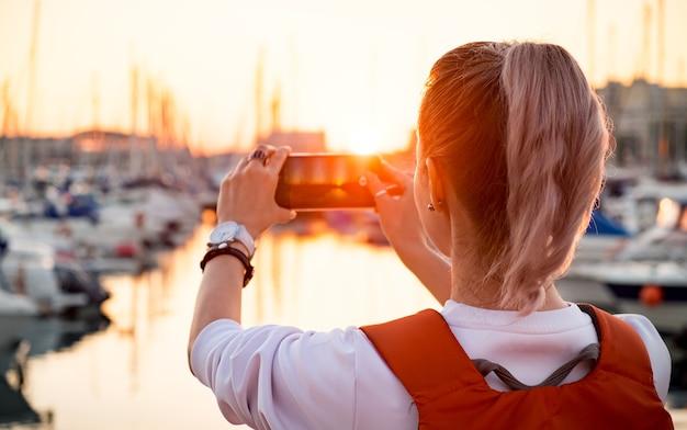若いかわいい女の子が日没時にヨットで湾の写真を撮っています