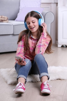 Молодая красивая девушка слушает музыку на полу в своей комнате
