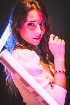 검정색 배경에 분홍색과 파란색 led 조명으로 매혹적인 시선으로 카메라를 보고 있는 어린 예쁜 소녀