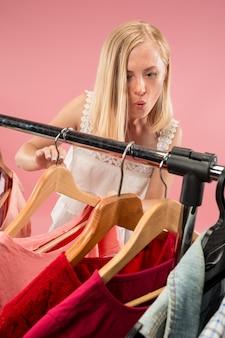 La giovane ragazza carina guarda i vestiti e prova mentre sceglie al negozio