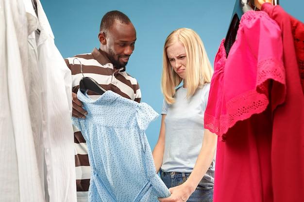 La giovane ragazza carina guarda i vestiti e prova mentre sceglie il negozio