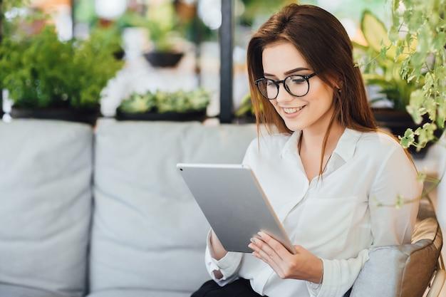 Молодая красивая девушка смотрит на планшет на летней террасе кафе.