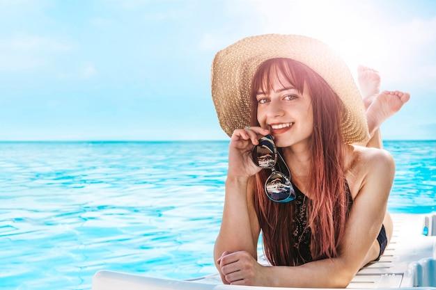 帽子をかぶって日光浴をしている若いかわいい女の子。遠く離れた熱帯のビーチと国。旅行のコンセプト。海での休暇中の観光客。日光の下でかわいい笑顔のモデル。テキスト用の空のコピースペース