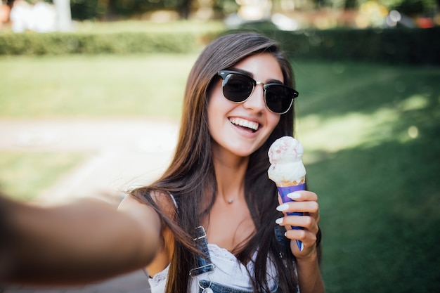 Young pretty girl makes selfie smiles with white teeth and holds the ice cream wearing sunglasses