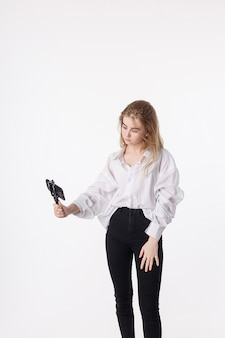 Young pretty girl making self portrait with smartphone attached to small tripod
