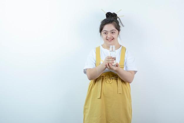 젊은 예쁜 여자 모델 서 흰색 벽에 유리 병을 들고.