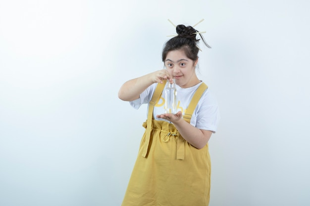 白い壁にガラス瓶を立って保持している若いかわいい女の子モデル。