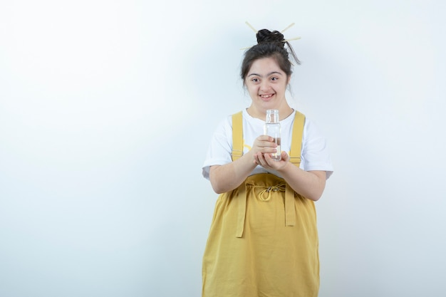 Young pretty girl model standing and holding glass bottle against white wall .