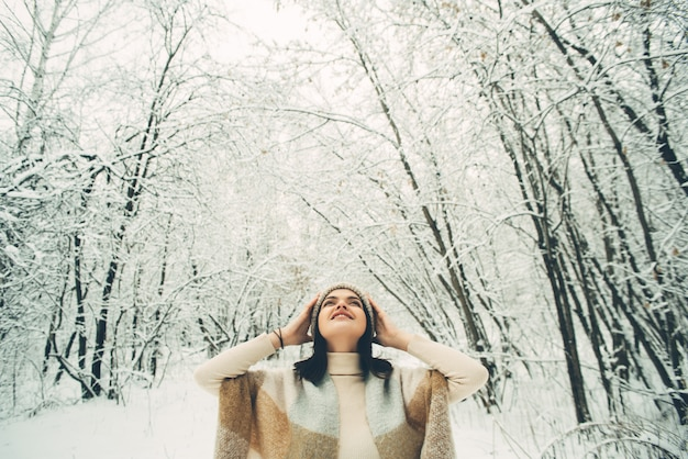 Young pretty girl under a plaid in a snowy forest, looking up. winter mood.