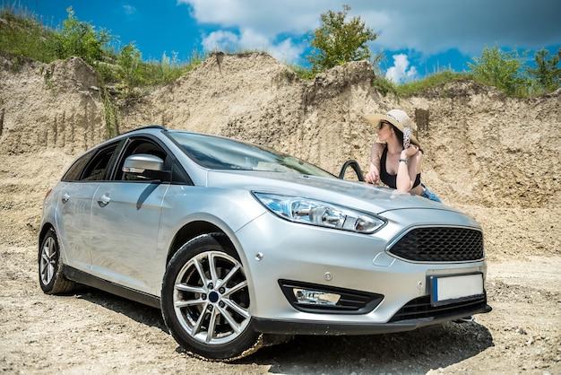 夏の旅行中に砂の採石場で車の近くでポーズをとる若いかわいい女の子