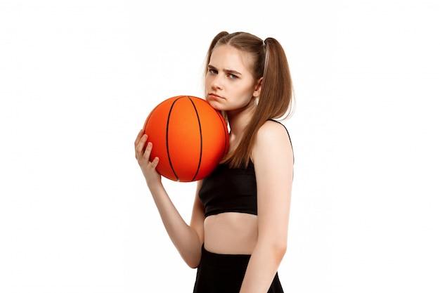 Молодая красивая девушка позирует с баскетболом, изолированных на белой стене