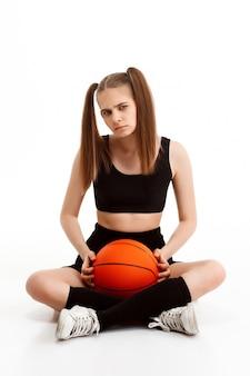 Молодая милая девушка представляя с баскетболом над белой стеной