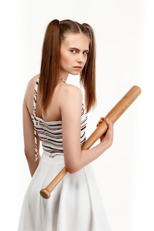 Young pretty girl posing with bat, isolated on white wall