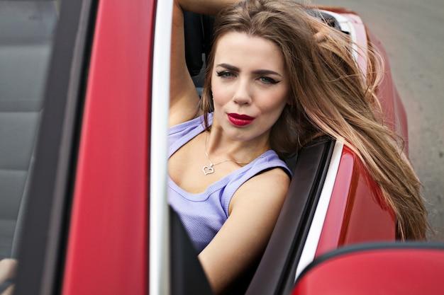 Young pretty girl in red cabrio